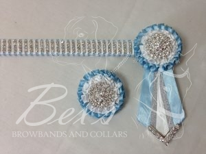 "3/4"" Crystal Show Browband: Light Blue satin background, 4 rows of Silver crystal chain woven on with White satin. Pleated rosettes with plain Silver centres. V shaped tails with Silver crystal flag tips. Shown here with a matching buttonhole."