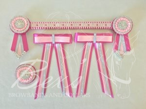 "3/4"" Crystal Show Browband: Garden Rose satin background with Silver three row patterned Crystal chain woven on with Light Pink satin. Pleated rosettes with plain Silver double row crystal rings and centres. V shaped tails with Silver crystal flag tips. Shown here with a matching buttonhole and large double hair bows."